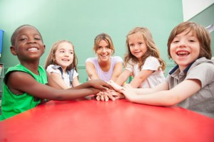 Teacher and children with hands together